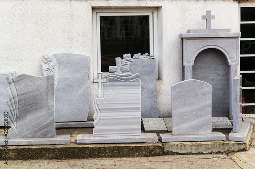 Small private firm produces tombstones and exhibites samples of its products on the street. - 252928893
