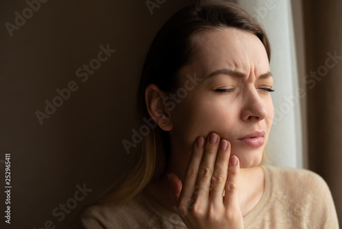 Toothache, and dentistry. Beautiful young woman suffers from terrible severe pain in her teeth, touching her cheek with her hand. Toothache in a woman. Dental care and health concept, dark background