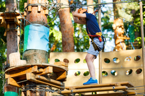 Cute young boy in helmet with climbing equipment in the rope amusement park. Summer camp, holidays concept