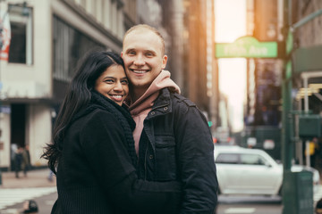 Happy young adult multicultural couple in love hugging and smiling on New York City street