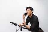 Businessman answering mobile phone while standing with bicycle