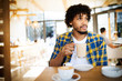 Starting new day in cafe. Side view of young african man holding coffee cup a