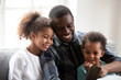 Leinwanddruck Bild - Happy black dad play on smartphone with little daughters