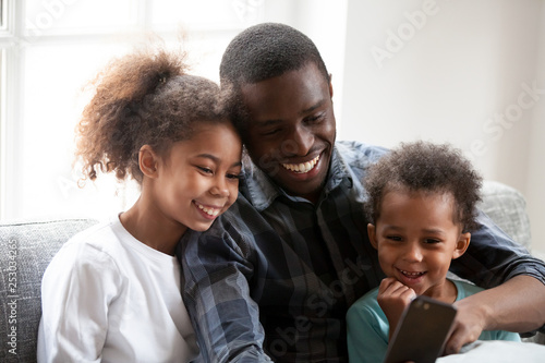 Leinwanddruck Bild Happy black dad play on smartphone with little daughters