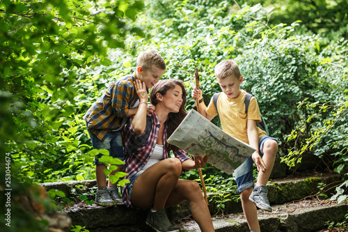 Mother and her little sons hiking .They taking a break and sitting on the old stairs.Examining map. © SolisImages