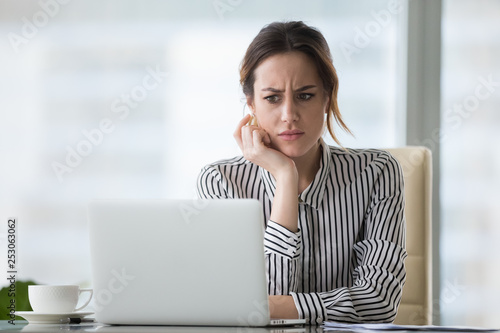 Confused businesswoman annoyed by online problem looking at laptop - 253063062