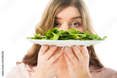 selective focus of woman holding plate with green spinach leaves isolated on white