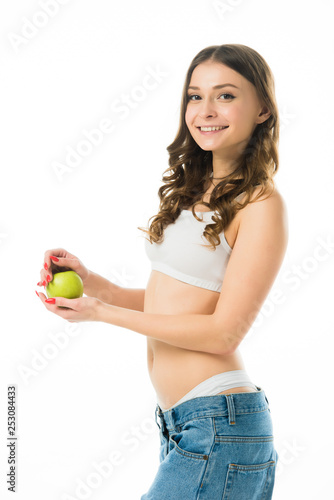 side view of smiling slim young woman in big jeans holding green apple isolated on white