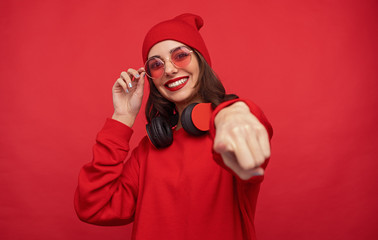 Trendy bright girl in red clothes pointing at camera