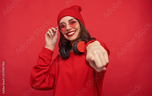 Leinwanddruck Bild Trendy bright girl in red clothes pointing at camera