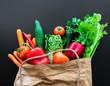 fresh organic vegetables in brown paper bag against dark table background