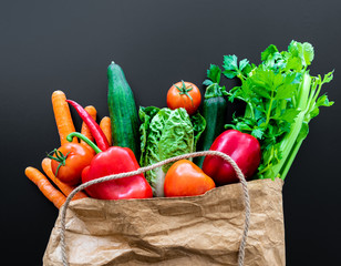 fresh organic vegetables in brown paper bag against dark table background