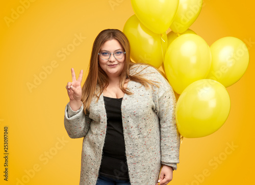 Plus size lady with balloons showing V sign