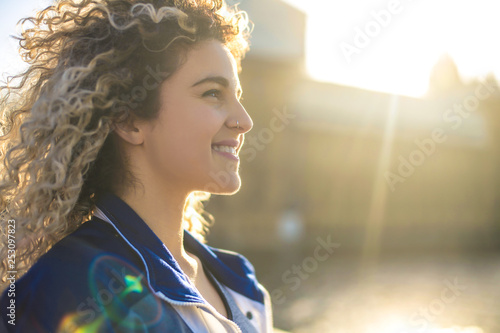 obraz lub plakat Beautiful girl with blonde curly hair, walking in the street