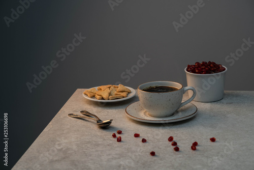 a hot drink of black coffee, homemade cookies and pomegranate seeds on a grey marble table, dark background © Olga Barilo