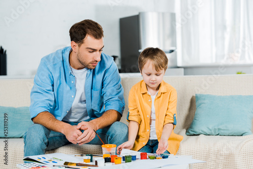 father and preschooler son sitting with art supplies during drawing at home