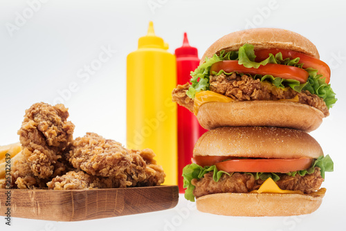 selective focus of crispy chicken nuggets and chicken burgers near bottles with ketchup and mustard isolated on white