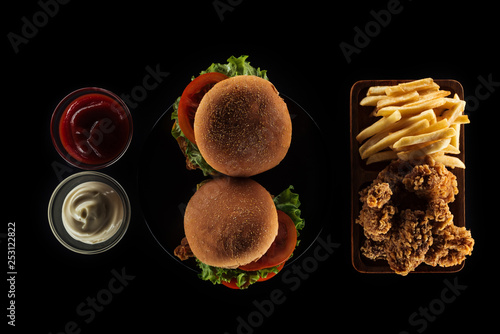 top view of tasty unhealthy food isolated on black