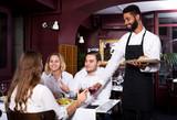 Restauracja średniej klasy i wesoły kelner