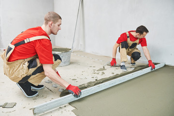 Floor cement work. Plasterer smoothing floor surface with screeder