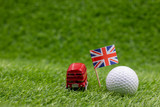 Double decker bus with golf ball on green with Union Jack flag
