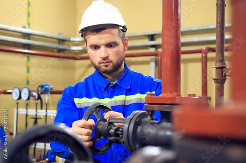 Worker turning gate valve on boiler pipe