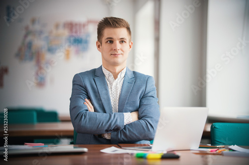 Young businessman working with laptop at office. Arms crossed on chest