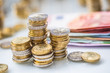 Euro banknotes and coins togetger on white table - close-up