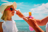sun protection - mom put suncream on little girl face at beach