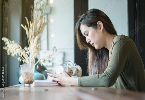Closeup asian woman use a smart phone and drinking iced chocolate at the wooden counter desk in coffee shop with happy face on coffee shop view background under window light