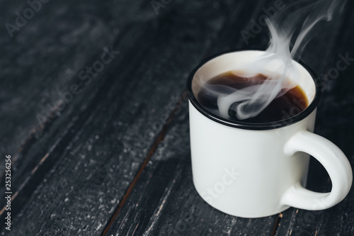 A mug of strong aromatic coffee on a dark wooden table with steam - 253256256