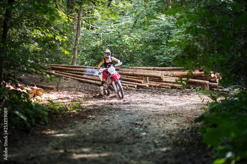 Female motocross rider accelerating into a corner in the woods