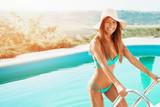 Beautiful, attractive woman enjoying near the pool