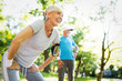 Leinwanddruck Bild - Happy mature couple stretching during running in the park