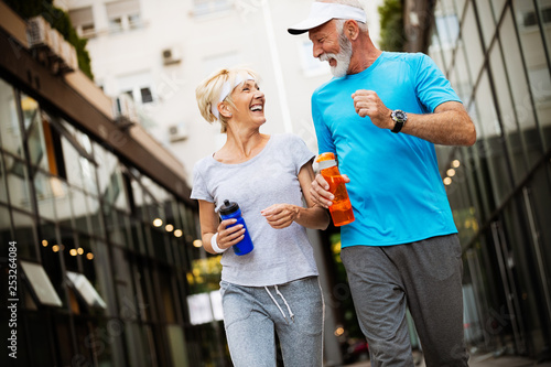 Leinwandbild Motiv Healthy senior, couple jogging in the city at early morning with sunrise