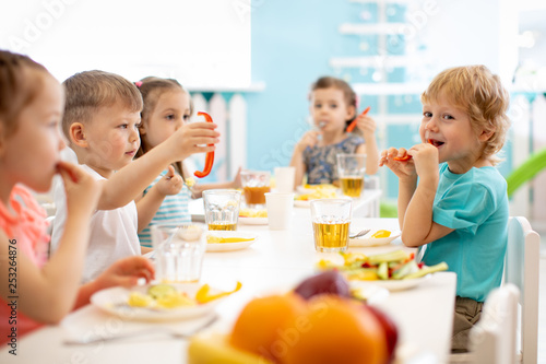 Group of kindergarten students eating healthy food lunch break together - 253264876