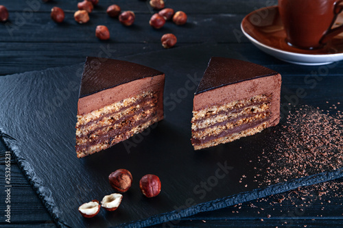 Close up view on sliced hazelnut cake with cacao on a black background and a plate. Flat lay sweets. Picture for menu, background or design with copy space. Sweet dessert. Chocolate cake