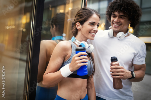 Young man and woman having break after running workout and drinking water