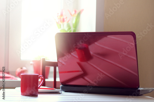 red cup of coffee and a notebook on the table are reflected in the lid of the laptop against the background of the window.  day break