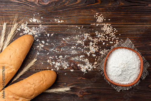Baguette and wheat on dark wooden background. - 253277638