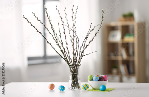 holidays and object concept - pussy willow branches and colored easter eggs in vase on table