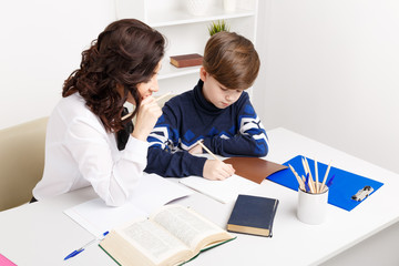 Female teacher helps teen boy to do his homework. Doing homework together