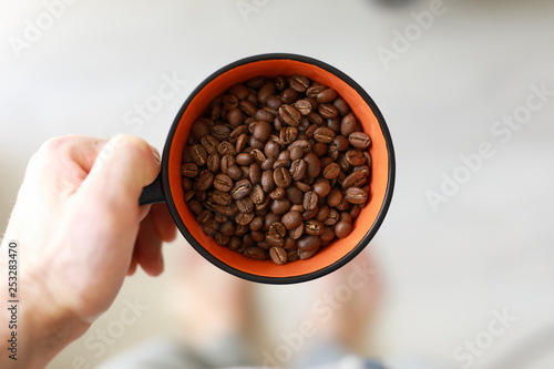 1-st person view, man holding cup with coffee beans © antgor