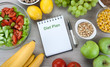 notebook with a diet plan with fresh vegetables and fruits on the table