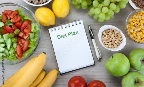 notebook with a diet plan with fresh vegetables and fruits on the table - 253286819