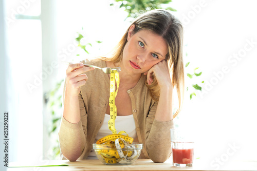 Worried beautiful woman holding fork with measuring tapes sitting in living room at home. - 253290222