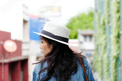 obraz lub plakat Back side of woman traveler standing with city outdoors background, casual lifesyle, travel blogger