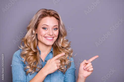 Close up photo glad amazing beautiful she her lady hold arms hands point empty space propose offer buy buyer new product wearing casual jeans denim shirt clothes outfit isolated grey background