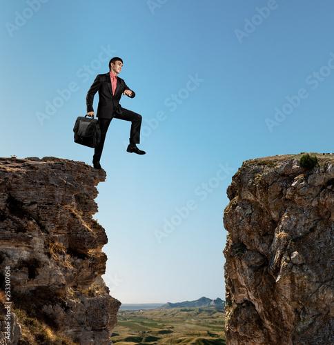 businessman walks through an abyss