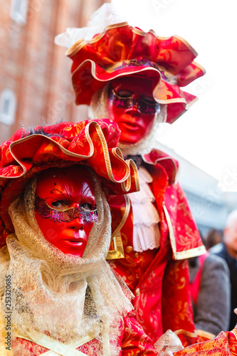 Venice Carnival 2019. San Marco Square. Venetian masked model on the laguna streets - 253320685